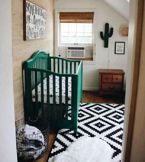 Quarto de bebê com berço verde e tapete geométrico preto e branco