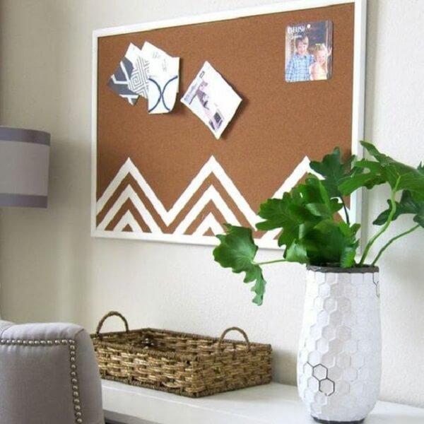 Quadro de cortiça com moldura branca se harmoniza com a decoração do ambiente