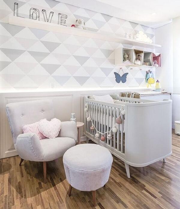 Quarto de bebê decorado com papel de parede geométrico e poltrona cinza de amamentação