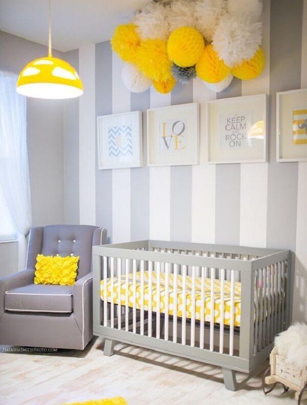 Quarto de bebê decorado com papel de parede listrado e poltrona cinza