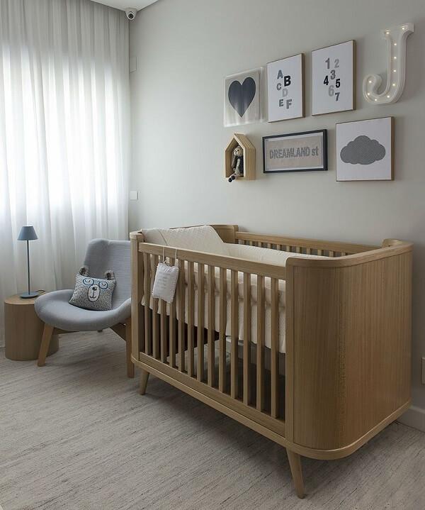 Quarto de bebê decorado com poltrona cinza de amamentação e berço de madeira