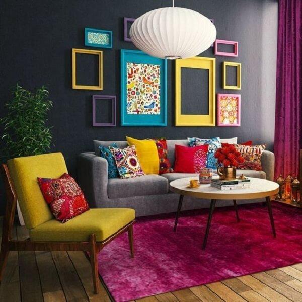 Sala colorida com cadeira amarela estofada, tapete rosa e almofadas estampadas