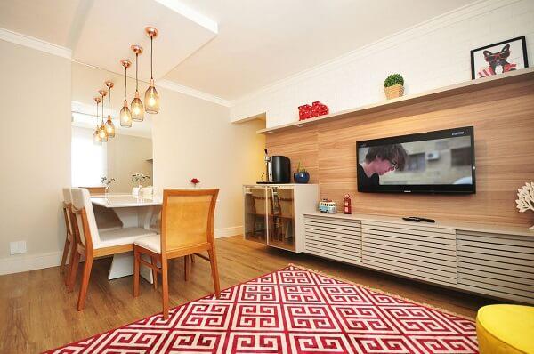 Sala com decoração branca, móveis de madeira e tapete geométrico vermelho