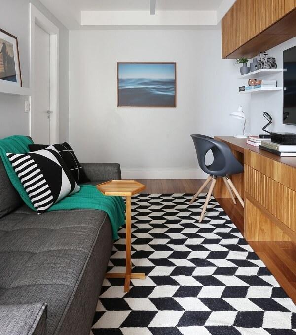 Sala compacta com sofá cinza e tapete geométrico preto e branco