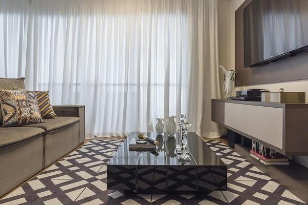 Sala de Tv com cortinas brancas e tapete geométrico