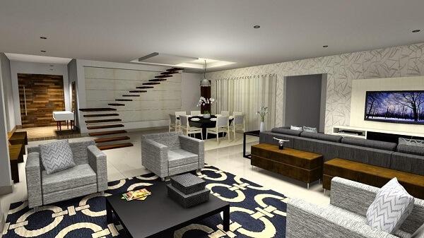 Sala de estar ampla com escada flutuante, poltrona cinza e tapete estampado