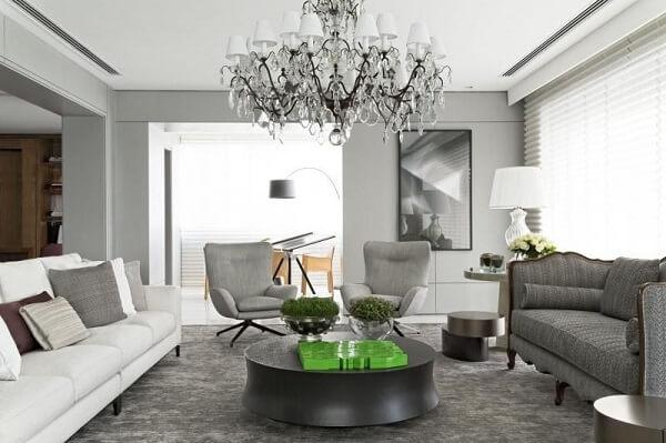 Poltrona para sala cinza e lustre de cristal complementam a decoração do ambiente