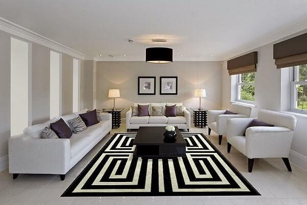 Sala de estar ampla com móveis claros e tapete geométrico preto e branco