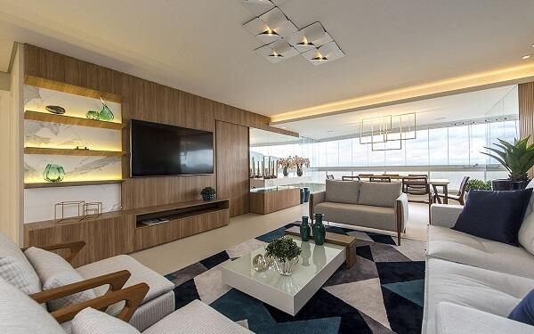 Sala de estar ampla com painel para Tv de madeira e tapete geométrico colorido