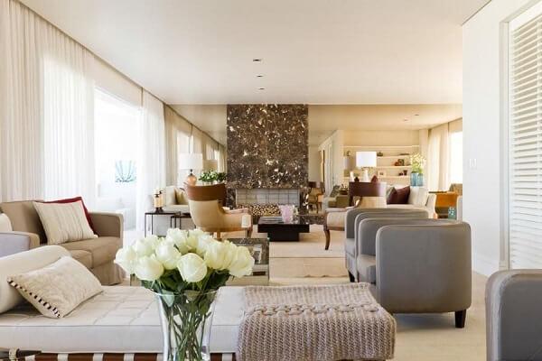 Sala de estar ampla com recamier e poltrona cinza