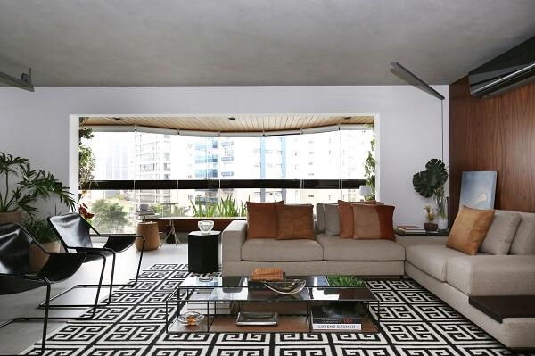 Sala de estar ampla com sofá de canto bege e tapete geométrico