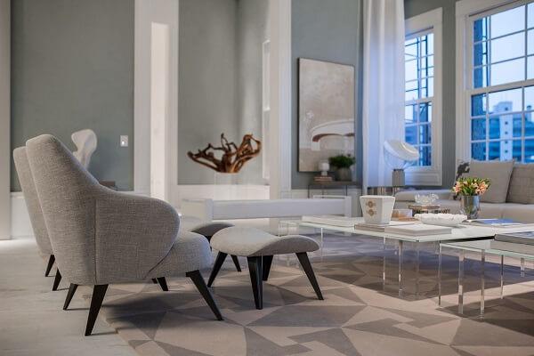 Sala de estar com decoração neutra, poltrona cinza e tapete geométrico