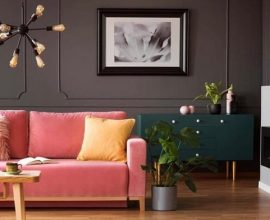 Sala de estar com pendente metálico e sofá rosa