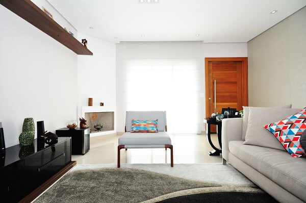 Sala de estar com poltrona cinza e almofadas estampadas