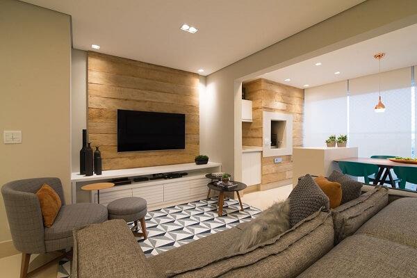 Sala de estar com poltrona cinza e tapete geométrico