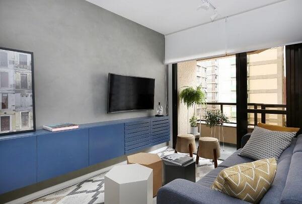 Sala de estar com rack azul e parede de cimento queimado