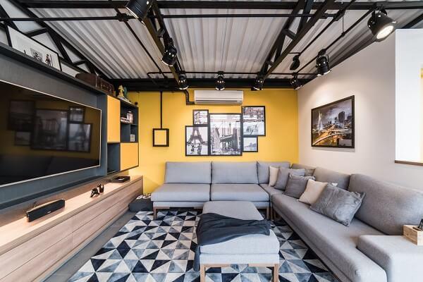 Sala de estar com sofá de canto cinza e tapete geométrico