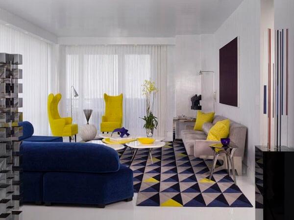 Sala de estar com tapete geométrico em tons de azul, cinza, preto e amarelo