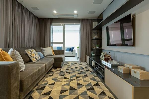 Sala de estar compacta com sofá cinza e tapete geométrico mesclado