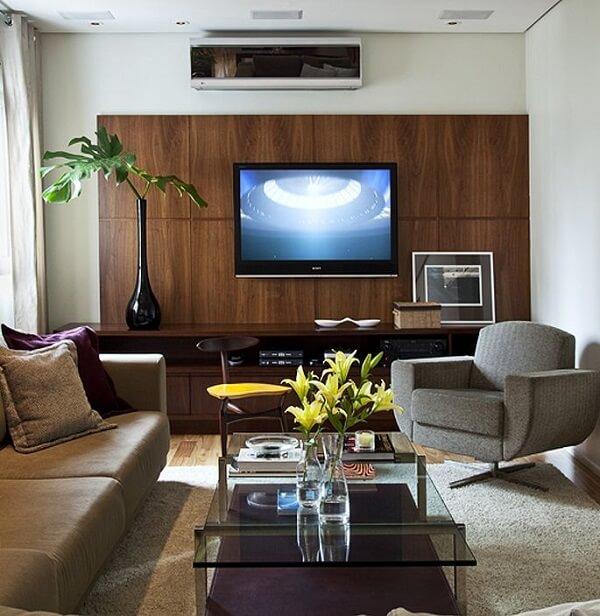 Sala de estar decorada com poltrona cinza giratória e mesa de centro de vidro