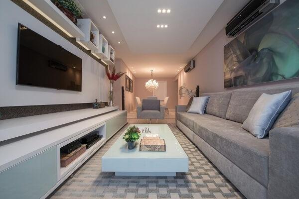 Sala de estar decorada com tapete geométrico, sofá e poltrona cinza