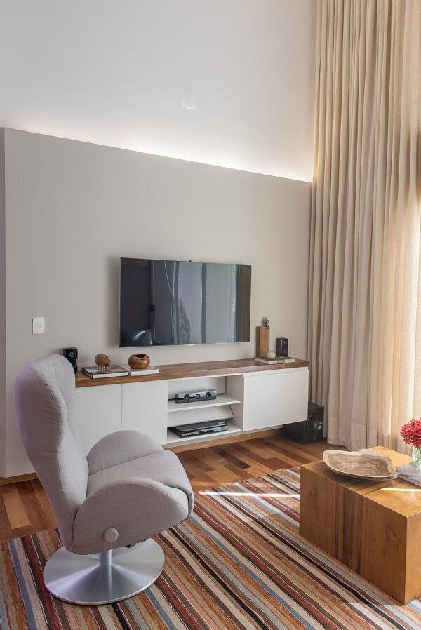 Sala de estar decorada com tapete listrado e poltrona cinza