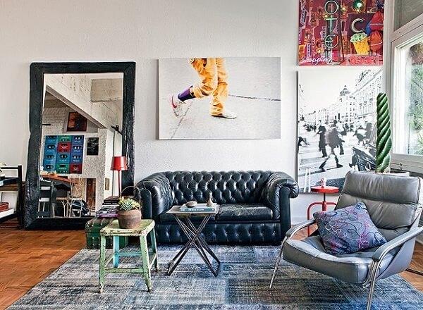 Sala de estar despojada com sofá capitonê preto e poltrona cinza