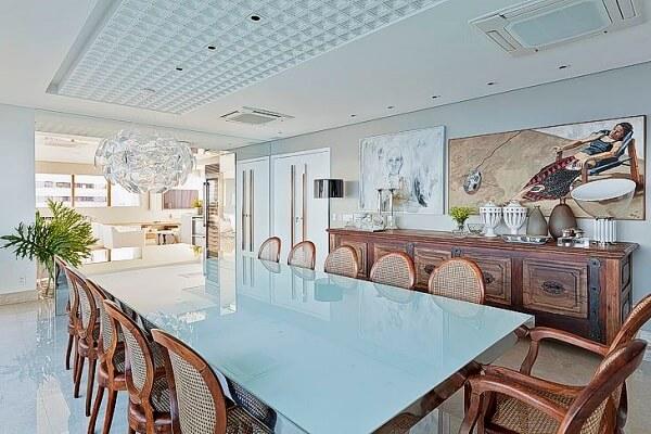 Sala de jantar ampla com mesa de vidro jateado e cadeiras de madeira