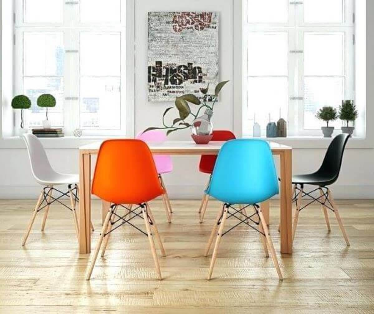 Sala de jantar decorada com mesa de madeira e cadeiras coloridas Foto Pinterest