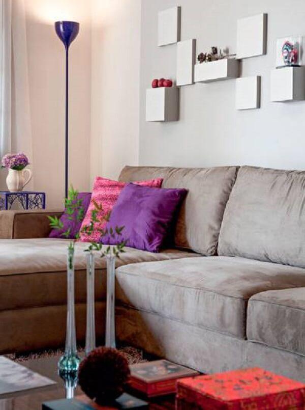 Sofá suede bege e almofadas em tom rosa e roxo