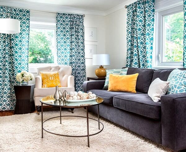 Sofá suede cinza chumbo e cortinas estampadas