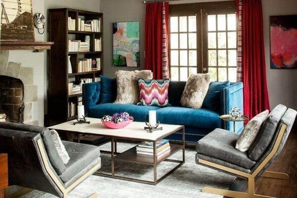 Sofá suede em tom azul com acabamento em capitonê