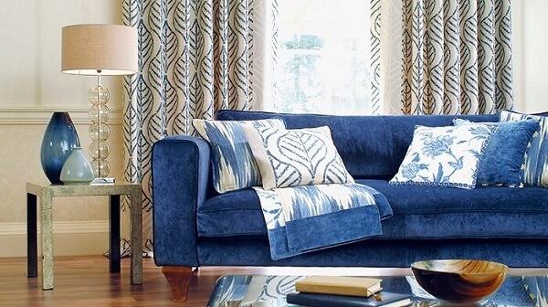 Sofá suede em tom azul e almofadas estampadas