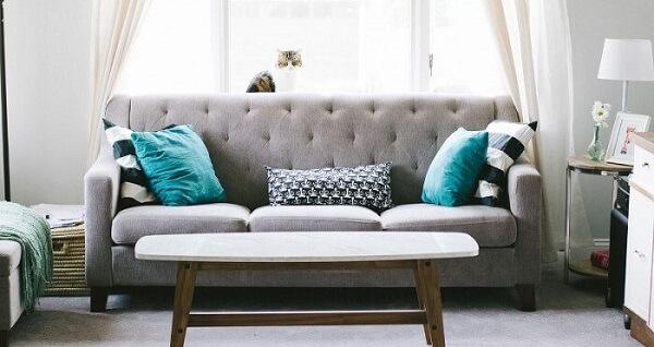 Sofá suede em tom cinza e mesa de centro de madeira