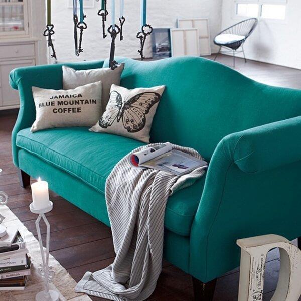 Sofá suede em tom esverdeado se destaca na decoração da sala de estar