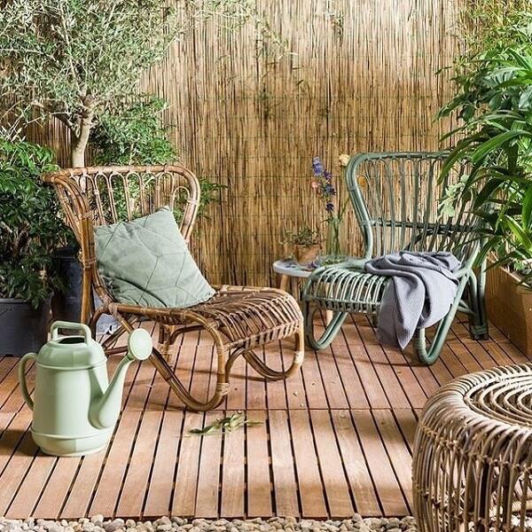 Terraço aconchegante com cerca de bambu e cadeira de madeira