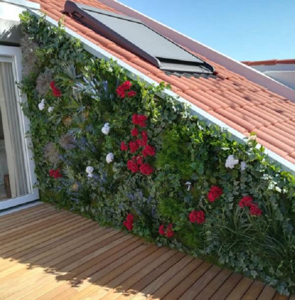 Terraço com jardim vertical artificial com flores