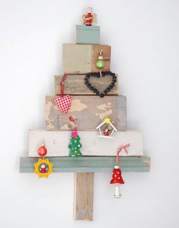 Tocos de madeira e enfeites formam a árvore de Natal na parede