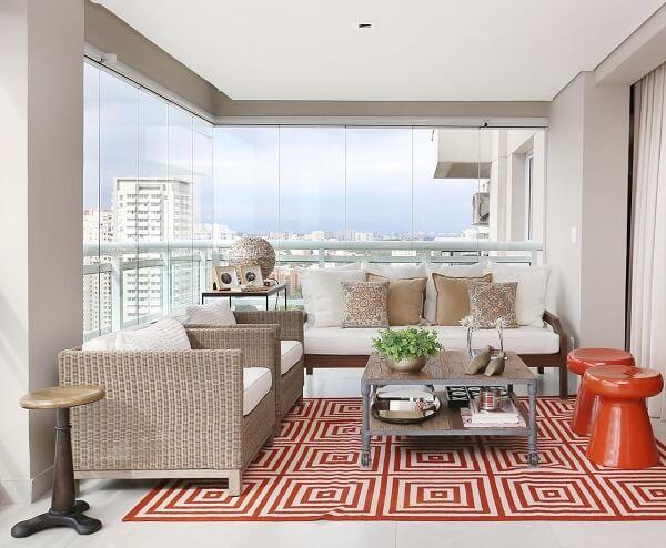 Varanda com sofá branco, poltronas e tapete geométrico vermelho