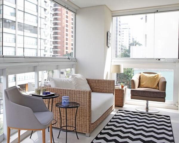 Varanda iluminada com sofá de vime e tapete geométrico em preto e branco