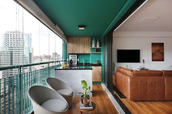 Varanda integrada decorada com teto verde, piso laminado de madeira e poltrona cinza claro