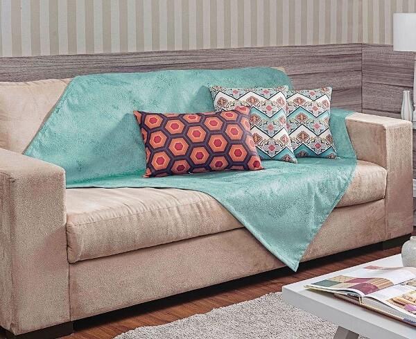 Xale azul sobre o sofá suede em tom bege