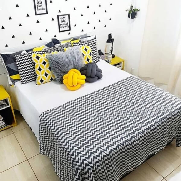 Almofada de nó em tons de cinza e amarelo se misturam com a decoração do ambiente