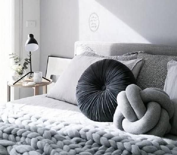 A almofada de nó em tom de cinza combina perfeitamente com a decoração clean do quarto