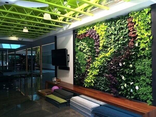 Os tons de verde do jardim vertical artificial se harmonizam com a cor do teto