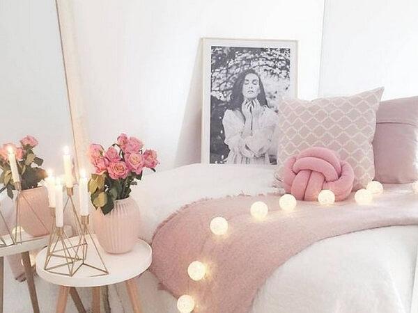 A almofada de nó rosa combina com os demais objetos do quarto