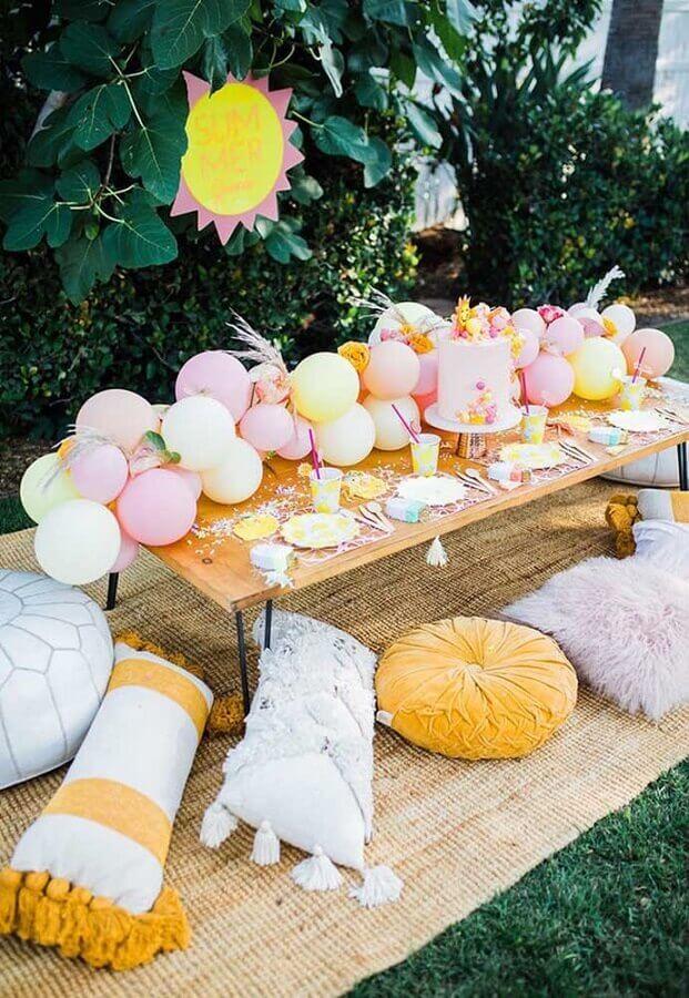 aniversário piquenique decorado com arranjo de balões e almofadas Foto Pinosy