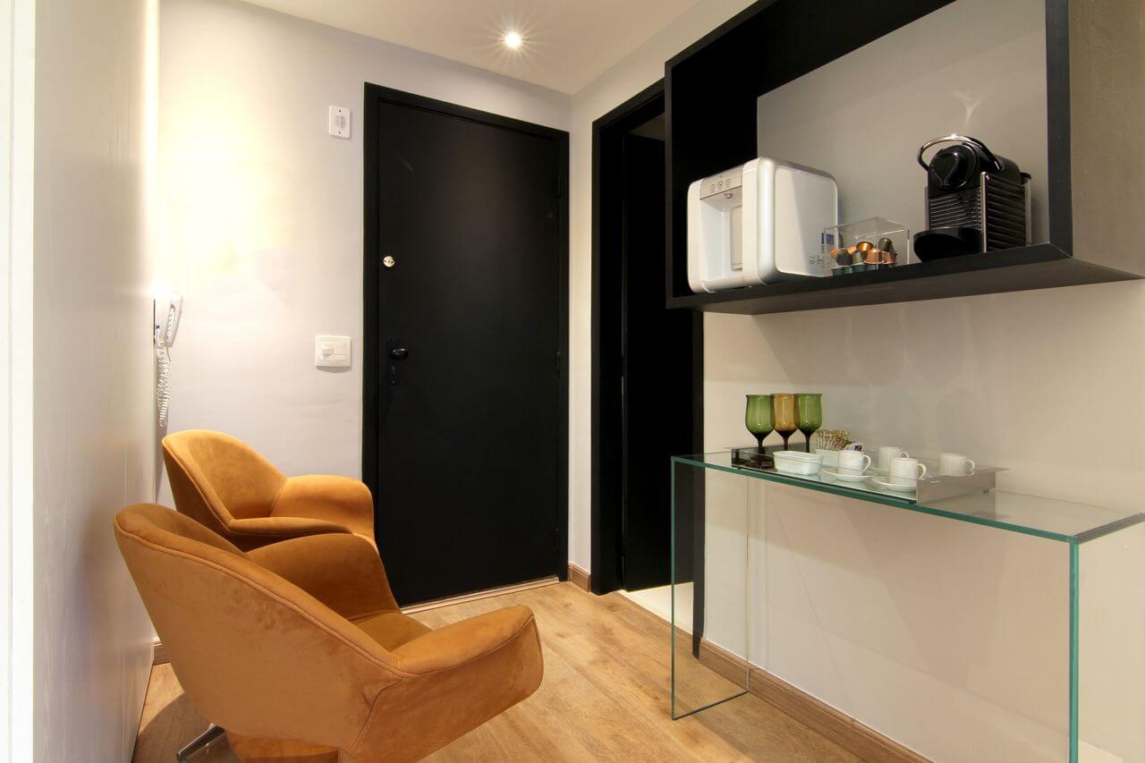 aparador de vidro - recepção com poltronas em ferrugem e porta preta