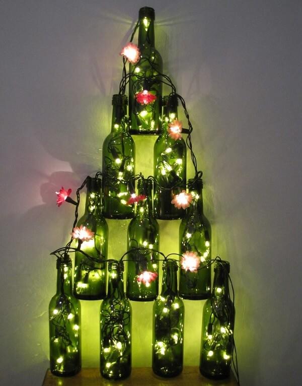 Árvore de Natal na parede feita com garrafas de vidro e pisca pisca