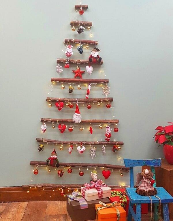 Árvore de Natal na parede feita com gravetos e enfeites natalinos